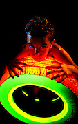 Young boy kneeling against glowing tire.Black light
