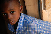 A young boy cools in the shade during church services in Accra, Ghana