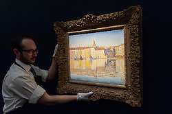 "© Licensed to London News Pictures. 08/04/2016. London, UK. A Sotheby's technician shows Paul Signac's ""Maisons Du Port, Saint Tropez"", 1892, est. $8-12million.  Sotheby's auction preview, at their New Bond Street gallery, of works to be in the upcoming New York Impressionist, modern and contemporary art sale. Photo credit : Stephen Chung/LNP"