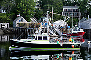 Lobster boats at a wharf piled high with lobster traps in New Harbor, Maine. The tiny picturesque pocket harbor is one of the last working harbors on the midcoast along the Pemaquid Peninsula