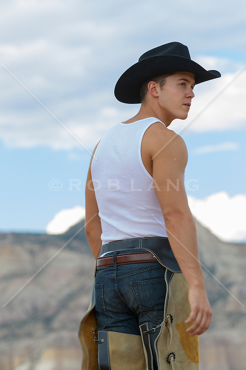 handsome young cowboy walking in the New Mexico landscape in chaps