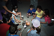Israel, Jordan Valley, Kibbutz Ashdot Yaacov, Lag Ba'Omer celebration with a bonfire. Children cooking marshmallows