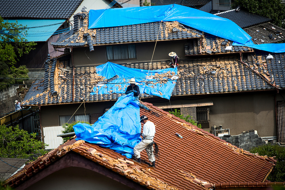 KUMAMOTO, JAPAN - APRIL 20 : Residents trying to fix the wreckage roof of houses on April 20, 2016 in Mashiki town, Kumamoto, Japan. At least 41 people were killed and over 180,000 people were evacuated in the series of earthquakes hitting southwestern Japan since 14 April 2016.<br /> Photo: Richard Atrero de Guzman