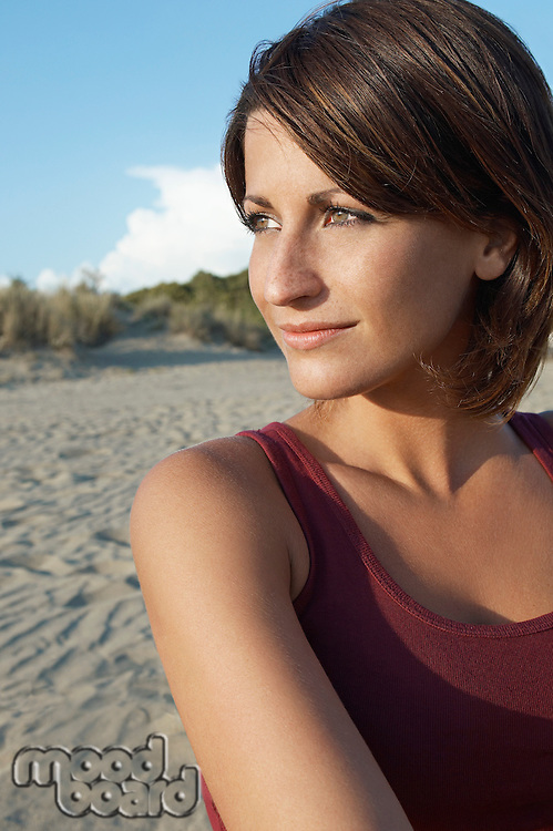 Portrait of young woman on beach looking away