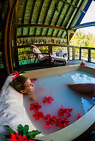 A woman relaxing in the soaking bath on the outdoor terrace of the Kahaia spa suite at the Spa in the Four Seasons Resort Bora Bora, French Polynesia.
