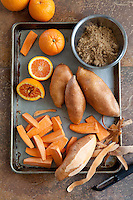 A tray of ingredients for a roasted sweet potatoes recipe including brown sugar, sweet potatoes, and oranges.
