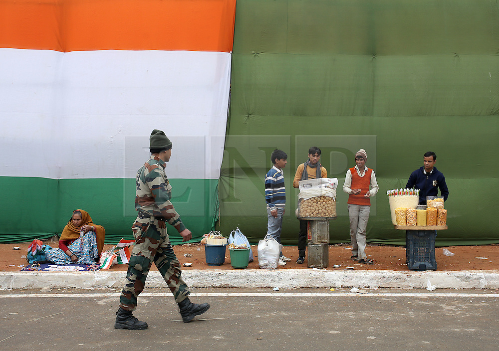 © Licenced to London News Pictures. 26//01/2015. Delhi. India.  <br /> A soldier walks past food vendors at India Gate on Republic Day in New Delhi, India, January 26th 2015. President Barack Obama was the chief guest in a show of solidarity between the world's two largest democracies in the face of an increasingly assertive China.<br /> Photo Credit: Susannah Ireland