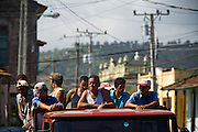 A group of men ride in the back on a truck in Baracoa, Cuba on Monday July 14, 2008.