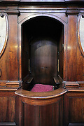 close up of a confessional with cushion for the priest to sit on