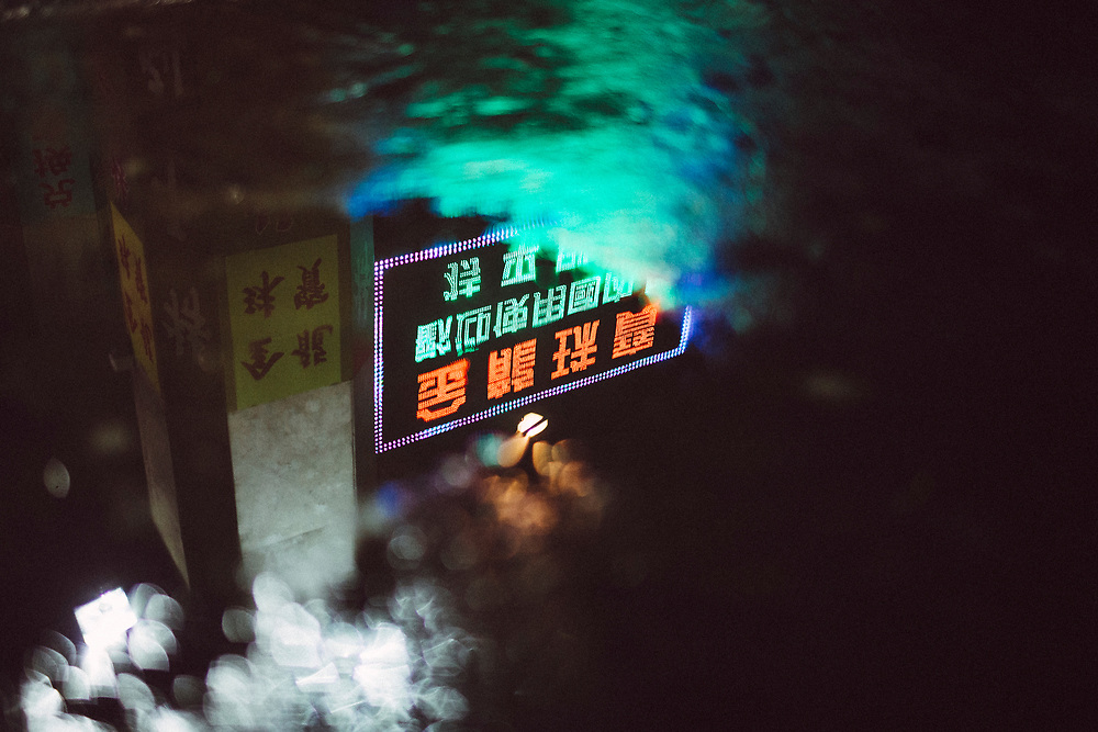 Neon lights reflected in a puddle in Macao.
