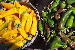 yellow and green peppers in baskets at a farmers market