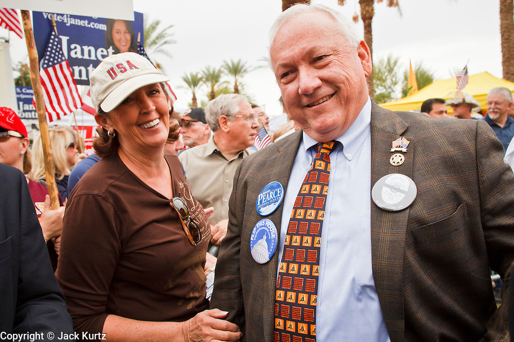 22 OCTOBER 2010 - PHOENIX, AZ:  Arizona State Senator RUSSELL PEARCE, a Republican and Tea Party supporter, RIGHT, talks to a supporter at a Tea Party rally in Phoenix. Pearce is a staunch opponent of illegal immigration and the author of SB 1070, Arizona's tough anti-illegal immigration bill. About 300 people attended a Tea Party rally on the lawn of the Arizona State Capitol in Phoenix Friday. They demanded lower taxes, less government spending, repeal of the health care reform bill, and strengthening of the US side of the US - Mexican border. They listened to Arizona politicians and applauded wildly when former Alaska Governor Sarah Palin and her son, Trig, made a surprise appearance. The event was a part of the Tea Party Express bus tour that is crossing the United States.     Photo by Jack Kurtz