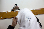 A young Palestinian girl prepares herself for school as she pins her headscarf in place using a tiny broken mirror that is on the wall at the UN school in Beit Hanoun in northern Gaza, December 30,2014. Thousands of Palestinians in Gaza are still displaced by the war . (Photo by Heidi Levine/Sipa Press).