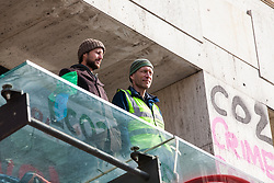 London, UK. 15th April 2019. Two climate campaigners from Extinction Rebellion continue to occupy an area above the main door to the Shell Centre during 'International Rebellion UK - Shut Down London!' in protest against the company's involvement in ecocide. Three fellow campaigners were earlier arrested after daubing graffiti on the exterior of the building, smashing a revolving door and glueing themselves to the door.