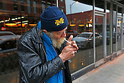 Homeless veteran Kenneth Bailey, who's street name is Wulf, lights a cigarette outside of the Bistro Market on Wednesday, Jan. 6, 2016 in downtown Springfield. Wulf was at the Bistro to eat dinner, charge his cellphone and wait for his friend so they could take the bus to the spot where they sleep.