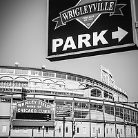 Wrigleyville Sign and Wrigley Field in black and white. Home to the Chicago Cubs, Wrigley Field is one of the oldest baseball stadiums in the United States. Wrigleyville is a popular area of Chicago with a multitude of bars and restaurants.