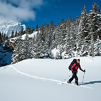 backcountry skiier with backpack skiing running eagle falls, glacier national park, montana
