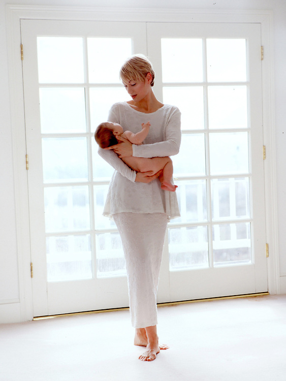 Mother with naked baby cradled in her arm in a white room.