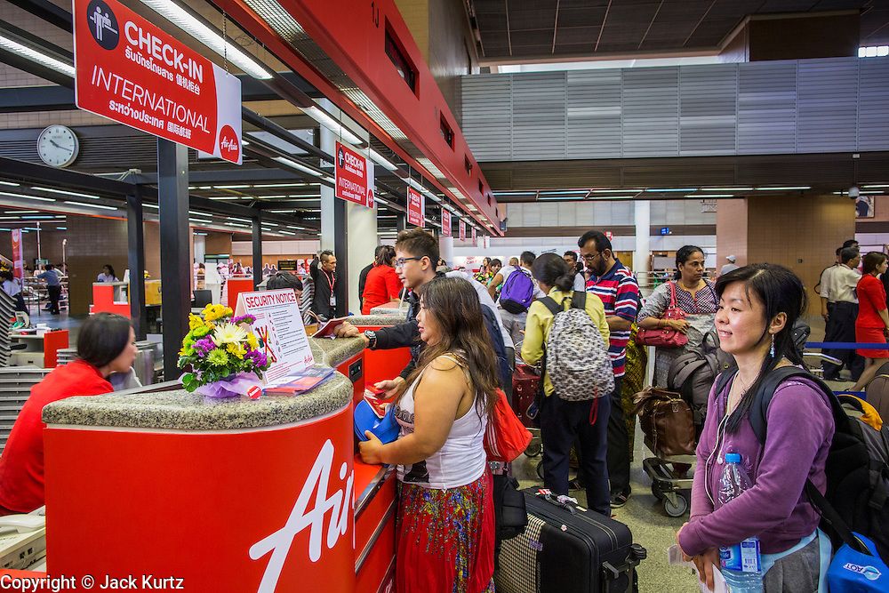 01 OCTOBER 2012 - BANGKOK, THAILAND:   People check in at the Air Asia counter in Don Mueang International Airport in Bangkok Monday. Don Mueang International Airport is the smaller of two international airports serving Bangkok, Thailand. Suvarnabhumi Airport, opened in 2006 is the main one. Don Mueang was officially opened as a Royal Thai Air Force base on 27 March 1914 and commercial flights began in 1924. Don Mueang Airport closed in 2006 following the opening of Bangkok's new Suvarnabhumi Airport, and reopened as a domestic terminal for low cost airlines after renovation on 24 March 2007. Closed during the flooding in 2011, Don Mueang was again renovated and reopened in 2012 as the airport for low cost airlines serving both domestic and international passengers. On Monday, Air Asia, Asia's leading low cost airline, transferred all of their flight operations to Don Mueang and the airport was officially reopened. Suvarnabhumi International Airport is already over capacity and Don Mueang's importance as a hub is expected to grow.  PHOTO BY JACK KURTZ