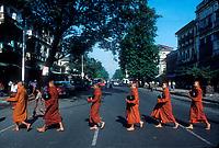 Buddhist monks cross the street on their way to receive offerings of food, in Rangoon (Yangon), Myanmar (Burma)<br /> Photo by Owen Franken