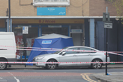 © Licensed to London News Pictures. 03/04/2017. LONDON, UK.  A forensic tent at the crime scene and police cordon around BJ Wines in Freemasons Road, Canning Town, east London. Ahmed Jah, 21 is reported to have been knifed inside the off license, BJ Wines in Freemasons Road yesterday afternoon after he was set upon by a gang of men and stabbed in the chest. Emergency ambulance services attended and the man was pronounced dead at the scene shortly after.  Photo credit: Vickie Flores/LNP
