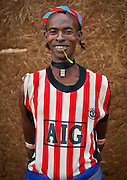 The football stars of tomorrow<br /><br />Thousands of Football shirts of Arsenal, Manchester, Chelsea, Milano, etc end up their carreer in... Ethiopia. Sold in the deep south, in the Omo Valley, those second hand clothes are bought by the local tribes. Most of them ignore the meaning of those shirts, and just buy them for the color, the logo, or the shape.<br />No warrior will go out without his little pillow/seat.<br />Some, like in Hamer tribe wear at the top of the head a clay helmet where they can put some ostrich feathers when they make a special action, like killing a wild animal, or...a man.<br />Those tribes won't exist in few years as the ethiopian governement has launched a huge plan to develop the area.<br />Soon, a highway coming from Mombassa - Nairobi will pass thru the villages to reach Addis Ababa.<br /><br />Photo shows: Tsamay tribe- Manchester United<br />©Eric Lafforgue/Exclusivepix Media