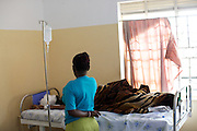 A patients carer by their bedside at Kasangati Health Centre in Uganda.<br /> <br /> Often patients have a carer travel with them to the hospital to look after them. It's their job to feed and look after the patient whilst they'e on the ward.
