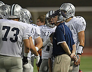 Xavier head coach Duane Schulte talks with his team during their game at Kingston Stadium in Cedar Rapids on Friday, September 27, 2013.