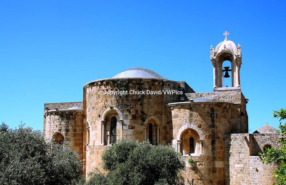 Historical stone church in Byblos, Lebanon features arches and ornate bell tower in the tourist district.