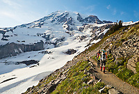 Climbers descending from Mount Rainier via the Skyline trail with the Nisqually glacier in the background. Washington, USA.