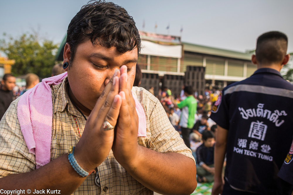 "15 MARCH 2014 - NAKHON CHAI SI, NAKHON PATHOM, THAILAND: A man prays after coming out of a trance state at the Wat Bang Phra tattoo festival. Wat Bang Phra is the best known ""Sak Yant"" tattoo temple in Thailand. It's located in Nakhon Pathom province, about 40 miles from Bangkok. The tattoos are given with hollow stainless steel needles and are thought to possess magical powers of protection. The tattoos, which are given by Buddhist monks, are popular with soldiers, policeman and gangsters, people who generally live in harm's way. The tattoo must be activated to remain powerful and the annual Wai Khru Ceremony (tattoo festival) at the temple draws thousands of devotees who come to the temple to activate or renew the tattoos. People go into trance like states and then assume the personality of their tattoo, so people with tiger tattoos assume the personality of a tiger, people with monkey tattoos take on the personality of a monkey and so on. In recent years the tattoo festival has become popular with tourists who make the trip to Nakorn Pathom province to see a side of ""exotic"" Thailand.   PHOTO BY JACK KURTZ"