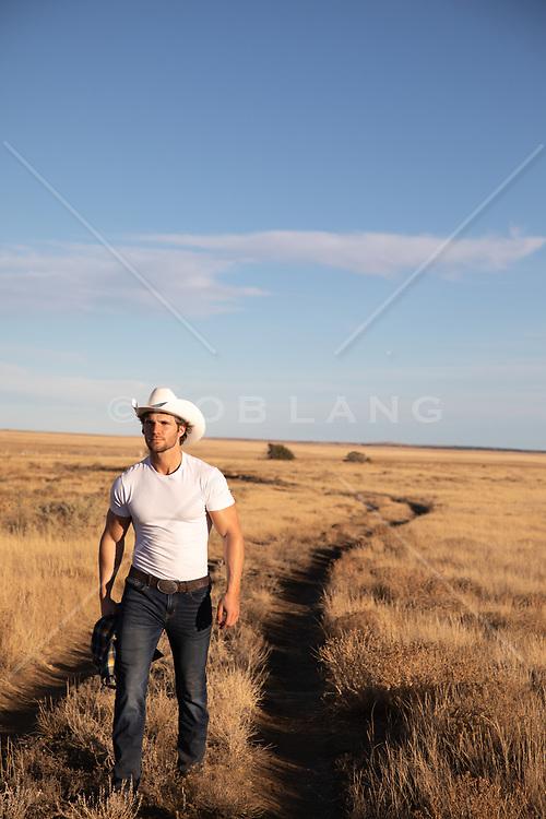 cowboy walking on a dirt road through a field