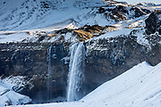 Tourists at spectacular Seljalands waterfall Seljalandsfoss in South Iceland with glacial melting waters from Eyjafjahajokull icecap