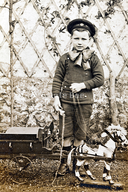 1900s little boy posing with wooden toy horse