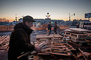 """Oleg (left) collecting wood for heating at the barricades blockading a building supplies store named """"Epicenter"""" in the city of Lviv, Ukraine."""