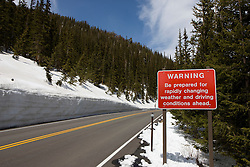 "Warning sign that reads ""Be prepared for rapidly changing weather and driving conditions ahead."" on The Trail Ridge Road, near Rainbow Curve.  The sides of the road are lined with evergreen trees and multi-foot banks of snow in mid-May, 2008  Rocky Mountain National Park (RMNP), founded by act of the US Congress in 1915, contains 72 named peaks above 12,000 feet in elevation including the tallest mountain peak in Colorado - Longs Peak at 14,259 feet.  The park, located next to Estes Park, CO, has five visitor centers and is traversed by the Trail Ridge Road (US highways 34 and 36).  Over 3 million visitors travel to the park annually to experience diverse mountain terrain, wildlife and recreation."