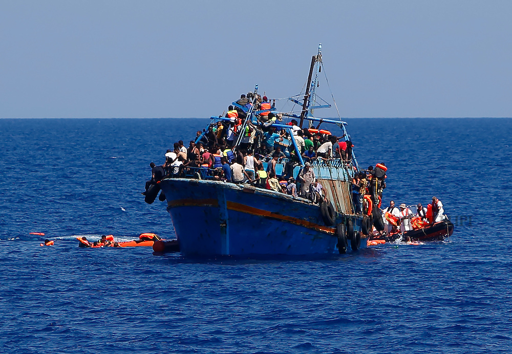 Migrants hang onto flotation tubes in the sea after jumping from an overloaded wooden boat during a rescue operation 10.5 miles (16 kilometres) off the coast of Libya August 6, 2015.  An estimated 600 migrants on the boat were rescued by the international non-governmental organisations Medecins san Frontiere (MSF) and the Migrant Offshore Aid Station (MOAS) without loss of life on Thursday afternoon, a day after more than 200 migrants are feared to have drowned in the latest Mediterranean boat tragedy after rescuers saved over 370 people from a capsized boat thought to be carrying 600.  Picture taken August 6, 2015.<br /> REUTERS/Darrin Zammit Lupi <br /> MALTA OUT. NO COMMERCIAL OR EDITORIAL SALES IN MALTA