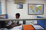 A clerk completes paperwork from a PC in the freight forwarding office of male International Airport, Maldives.