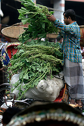 BANGLADESH DHAKA KAWRAN BAZAAR 27FEB05 - A customer loads his riksha with vegetables in the Kawran Bazaar vegetable market. The Bazaar has been in the Tejgaon area for at least 30 years and is one of the largest markets in Dhaka city...jre/Photo by Jiri Rezac ..© Jiri Rezac 2005..Contact: +44 (0) 7050 110 417.Mobile:  +44 (0) 7801 337 683.Office:  +44 (0) 20 8968 9635..Email:   jiri@jirirezac.com.Web:    www.jirirezac.com..© All images Jiri Rezac 2005- All rights reserved.