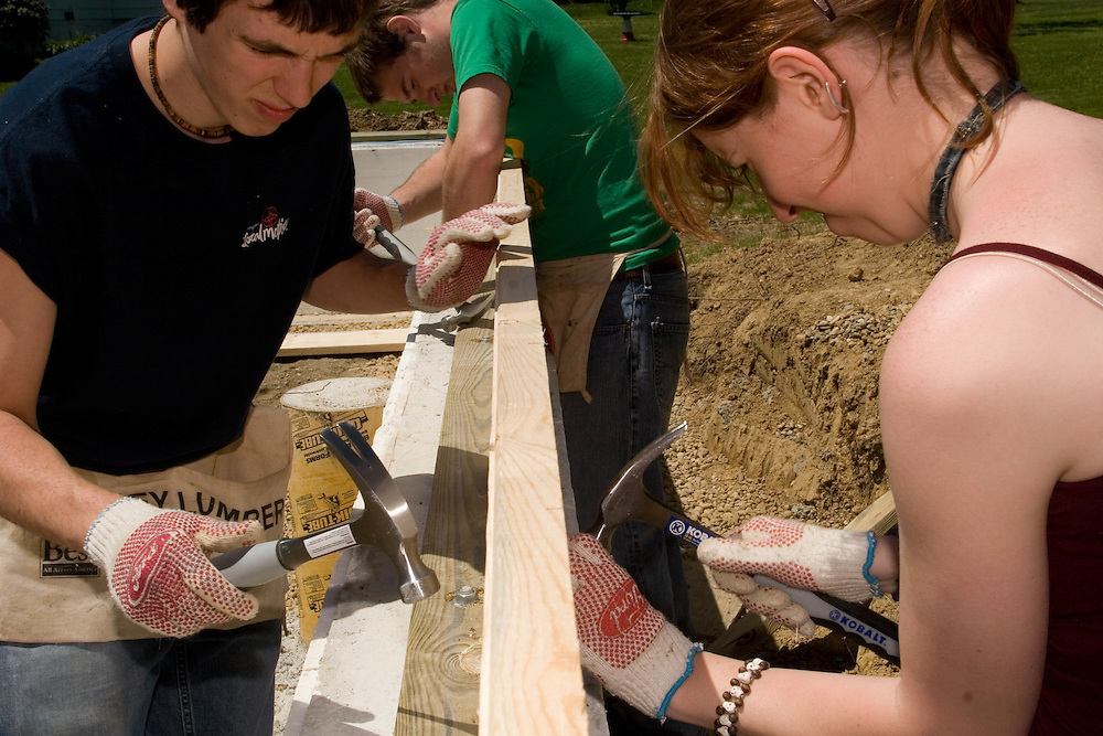 From left, Michael Kortlander, Leo Walter, and Jessica Beardsley, all members of the Honors Tutorial College, work on raising a home for Habitat for Humanity Friday, April 28, 2006 in The Plains.