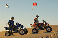 Men sitting on quad bikes in desert