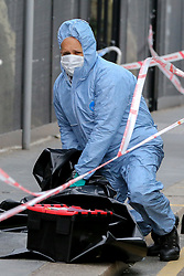 © Licensed to London News Pictures. 13/03/2019. London, UK. Forensic officer looking at the victims clothing at the crime scene outside Leyton Underground tube station in East London where a 17 year old boy was stabbed multiple times at 12.45pm. According to the Met Police, the victim is in a life threatening condition.  Photo credit: Dinendra Haria/LNP