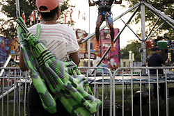 A woman caring multiple inflatable assault riffle style toys as she watches a child on a trampoline at a small community carnaval, in Wyndmoor, PA, just outside Philadelphia, on June 8, 2018.