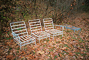 outdoor chairs with fall leaves waiting for spring to come