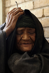 "Fakira Bader, 100, is seen at a retirement home in Sadr City, Baghdad, Iraq, July 22, 2003. Residents like Bader who have bouts of senility live a lonely life, they are left unattended as they wait to die. ""I don't know where I am from,"" said Bader. ""I have been here all my life.""  Even though most families in Iraq care for their aging relatives at home, there is still a need for the facility, which is the largest of its kind in Baghdad housing 45 women and 87 men. The facility was not looted during the war, but it is still lacks some funding and is in need of medications for patients with chronic conditions such as heart disease and diabetes."