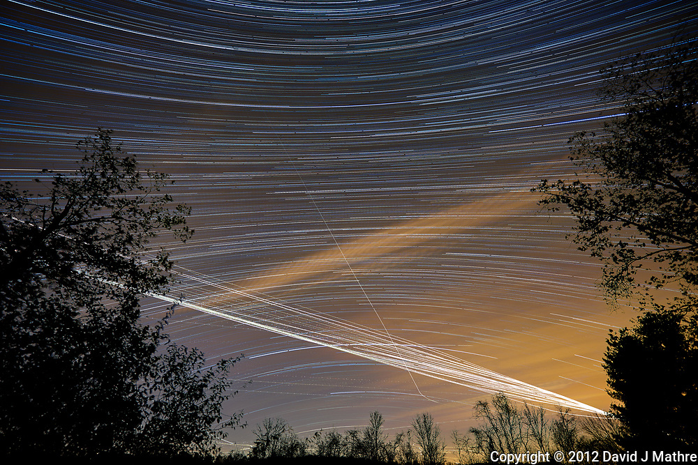 Southern backyard view of the night sky. Star trails, jet trails, and clouds. Composite of 180 images taken with a Nikon D800 camera and 14-24 mm f/2.8 lens (ISO 100, 14 mm, f/2.8, 59 sec).