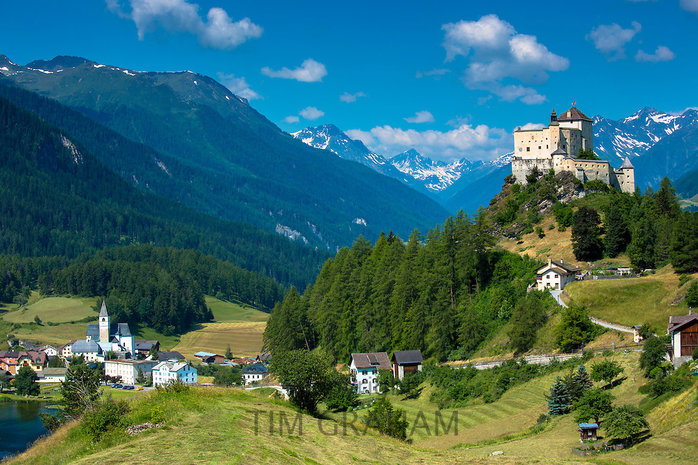 Tarasp Castle and Fontana village surrounded by larch forest in the Lower Engadine Valley, Switzerland
