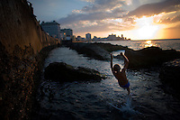 A child jumps into the sea along the Malecón in Havana, Cuba. ..With an aging Socialist dictatorship nearing it's end, Cuba is in a time of rapid change. The deterioration is taking it's toll on the island nation as it remains locked in the Cold War era time warp.  As restrictions on Cuba's population are beginning to be lifted by the changing government, new hope is brewing in the minds of the the citizens as they hope for a future full of opportunity.. Photographer: Robert Caplin