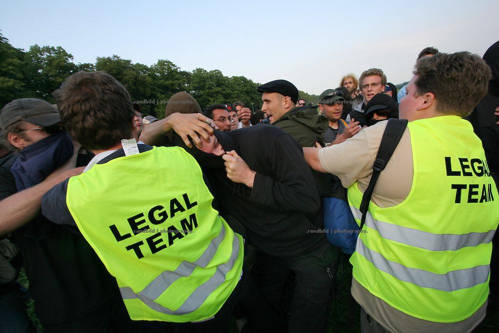 Während der Blockaden des G8-Gipfels wird ein mutmaßlicher Zivipolizist (Mitte), der als Autonomer verkleidet ist, von Demonstranten angegriffen. Andere Demonstranten versuchen die Attacken abzuwehren und übergeben den Mann später Polizeikräften.