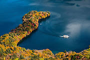 Tour boat on Lake Chuzenji (Chuzenjiko), a scenic lake in the mountains above the town of Nikko, in Tochigi Prefecture, Japan. It's at the foot of Mount Nantai, Nikko's sacred volcano, whose eruption blocked the valley below, thereby creating Lake Chuzenji 20,000 years ago. Chuzenjiko's shores are mostly undeveloped and forested except at the eastern end where the growing hot spring town of Chuzenjiko Onsen was built. Chuzenjiko is especially beautiful in mid to late October, when the autumn colors reach their peak along the lake's shores and surrounding mountains. See panoramic views of Lake Chuzenji along the Chuzenjiko Skyline, an eight kilometer long former toll road accessible by bus or car, which also connects to scenic hiking trails.
